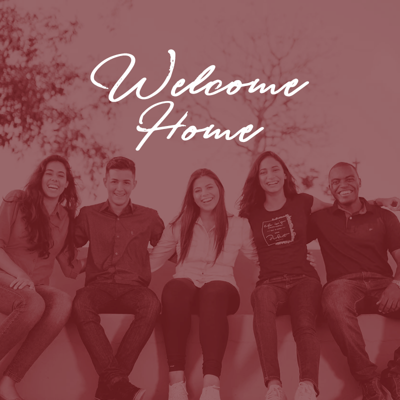 """A group of friends sitting below the words """"Welcome Home"""""""